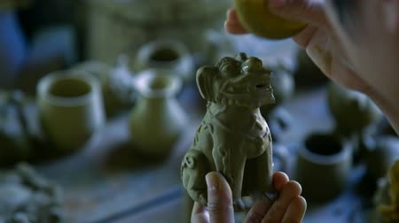 terracota : macro woman hands clean clay dog sculpture with sponge