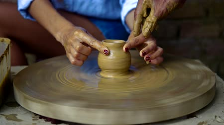 terrakotta : old potter guides lady fingers making clay pot on wheel