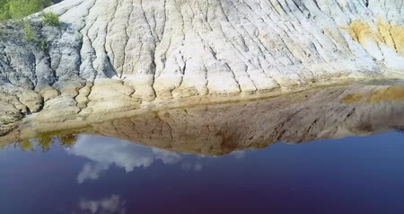 old pit : aerial steep slope sky cloud reflect in mirror lake on pit Stock Footage