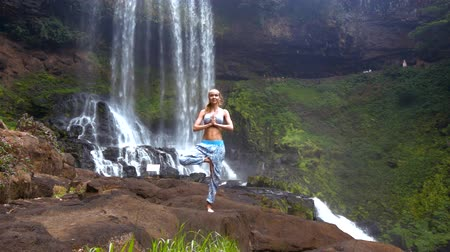 pliegues : girl holds pose on leg folds palms on chest at waterfall