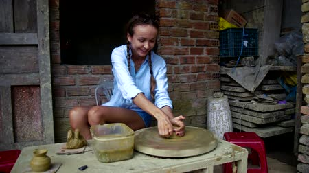 terracota : joyful girl makes clay pot at masterclass in asian shop