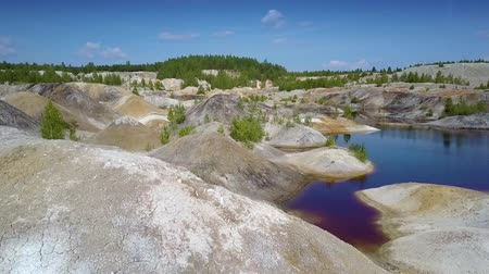 pedreira : motion above clay pit slope tops past lake to rare plants Stock Footage