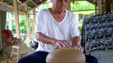 terrakotta : skilled senior potter in glasses grinds large clay pot