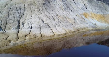 taş ocağı : camera shows wind-blown slope reflection in blue lake on pit