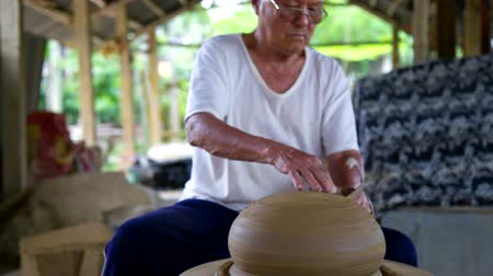 terracota : old potter master grinds big clay vessel with metal ring