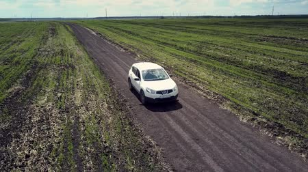suéter : white car drives along ground road among vast fields Stock Footage