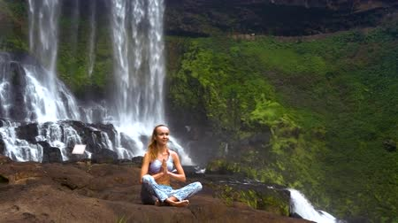 meditando : blond girl sits in pranayama yoga pose on rock at waterfall