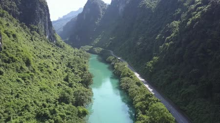 paralelo : aerial blue river and highway on bank meander in canyon