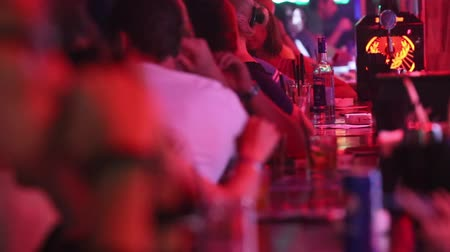 convidado : side view night club guests rest with cocktails at bar Vídeos