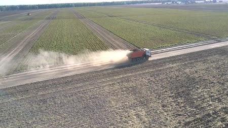 nakládané : flycam follows truck with potatoes driving along ground road