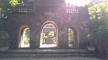 camera moves through huge stone gate to temple inner yard Vídeos
