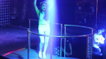 lacy : NHA TRANGVIETNAM - JULY 12 2015: Pretty Asian girl pop singer star in lacy top sings popular song in projector lights on nightclub podium on July 12 in Nha Trang Stock Footage