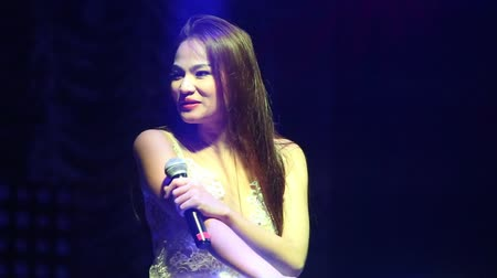 lacy : NHA TRANGVIETNAM - JULY 12 2015: Close view nice slim long haired Asian pop singer in lacy top speaks to public on club stage by railings on July 12 in Nha Trang
