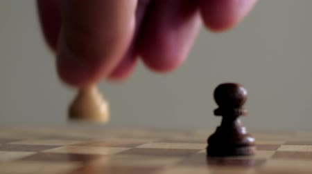 королева : interesting macro picture person fingers take white queen piece and capture black pawn on chessboard Стоковые видеозаписи