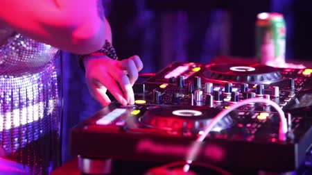 lever : NHA TRANGVIETNAM - JULY 25 2015: Closeup girl dj hand with tattoo moves levers on music mixer console playing music under flashing lights in nightclub on July 25 in Nha Trang Stock Footage