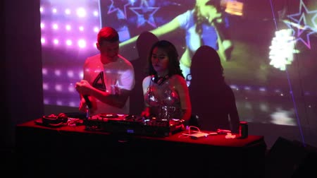 evsahibi : NHA TRANGVIETNAM - JULY 25 2015: Closeup dancing guy club host and girl dj at console entertain people against screen showing singer in nightclub  on July 25 in Nha Trang Stok Video