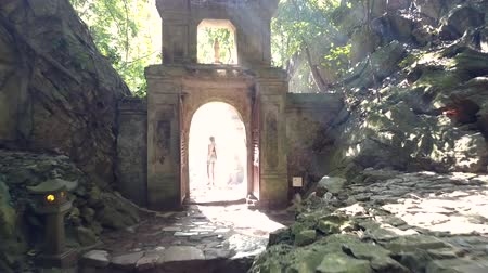 bum : backside view slim woman walks through gate in stone arch at large mountain against bright sunlight