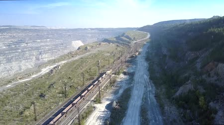 goederentrein : amazing upper view empty freight train on railway around huge asbestos quarry against clear sky in summer Stockvideo