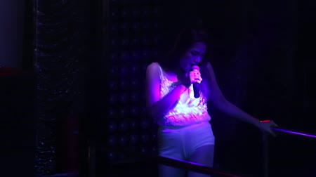 corrimão : NHA TRANGVIETNAM - JULY 12 2015: Pretty girl in white shorts and top sings popular song dancing on stage in modern dark nightclub on July 12 in Nha Trang
