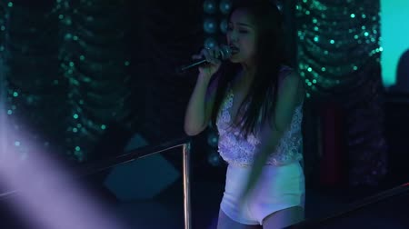 lacy : NHA TRANGVIETNAM - JULY 12 2015: Long haired Asian girl singer in lacy top sings popular song dancing in spotlights on nightclub stage on July 12 in Nha Trang