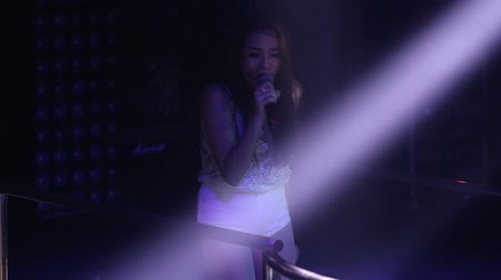 podyum : NHA TRANGVIETNAM - JULY 12 2015: Closeup famous asian pop star dances singing popular song in projector light rays in nightclub darkness on July 12 in Nha Trang Stok Video