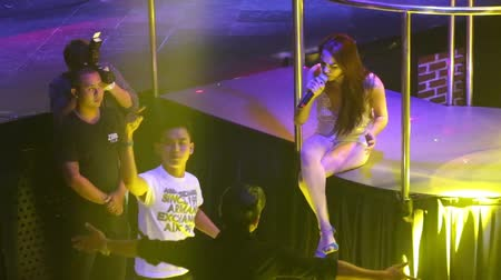 podyum : NHA TRANGVIETNAM - JULY 12 2015: Asian girl singer in white sits on stage and sings with guy spectator in popular night club on July 12 in Nha Trang
