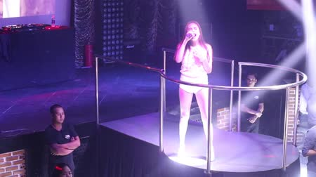 lacy : NHA TRANGVIETNAM - JULY 12 2015: Young beautiful Asian girl pop star in white lacy top performs popular song at party on club podium on July 12 in Nha Trang Stock Footage