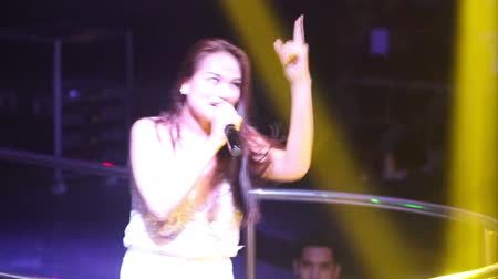lacy : NHA TRANGVIETNAM - JULY 12 2015: Close view nice slim long haired Asian pop singer in lacy top dances and sings on club stage by railings on July 12 in Nha Trang