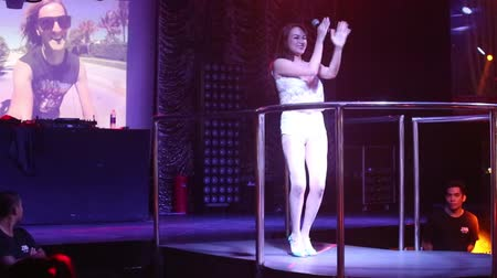 лечит : NHA TRANGVIETNAM - JULY 12 2015: Beautiful smiling asian girl pop singer on high heals dances at nightclub music party in projector lights on July 12 in Nha Trang Стоковые видеозаписи