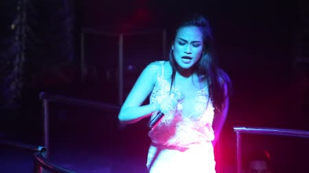 podyum : NHA TRANGVIETNAM - JULY 12 2015: Beautiful Asian girl pop singer star in white lacy top sings popular song at party on night club podium on July 12 in Nha Trang