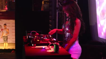 ターンテーブル : NHA TRANGVIETNAM - JULY 25 2015: Side view young attractive asian woman dj in shining top and short white skirt plays music set at party in club on July 25 in Nha Trang 動画素材