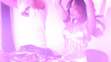mikser : NHA TRANGVIETNAM - JULY 25 2015: Close view pretty girl dj in silver top and guy in t-shirt jump dancing to music by mixer console in nightclub on July 25 in Nha Trang Stok Video