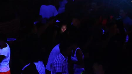 taniec : NHA TRANGVIETNAM - JULY 25 2015: Joyful young Asian clubbers dance and have fun on club floor under projector lights in popular nightclub on July 25 in Nha Trang