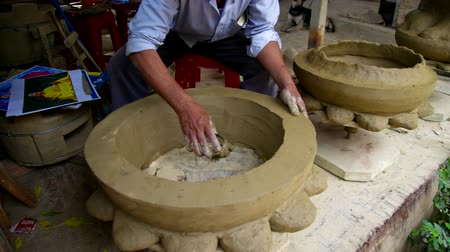 oleiro : HOIANVIETNAM - MAY 04 2018: Skilled asian potter makes huge clay footing for Buddhist saint master statue in pottery workshop on May 04 in Hoian Vídeos