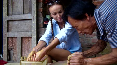 terrakotta : local skilled old master corrects tourist clay pot on potter wheel and girl watches at masterclass in souvenir workshop