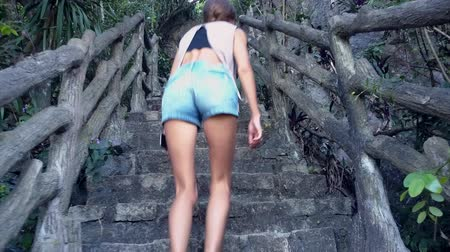vagabundo : backside view tired slim girl in denim shorts goes up stone steps with wooden handrail on hill