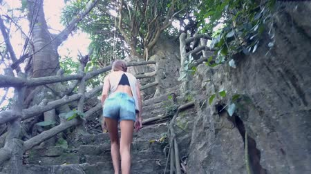 lépcsőfok : low angle shot long legged girl in denim shorts climbs up ruined stone steps with old railings in tropical park Stock mozgókép