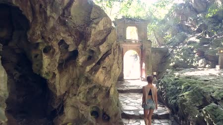 backside view girl in shorts walks past rocky walls and leaves cave through stone arch gate against sunlight Vídeos