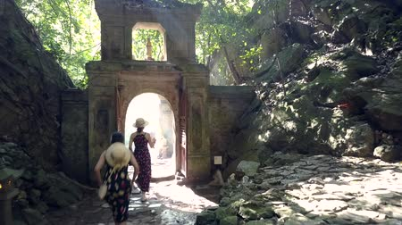 odejít : DANANGVIETNAM - MAY 05 2018: Backside view women tourists in straw hats leave cave through gate in stone arch against sunlight in park on May 05 in Danang