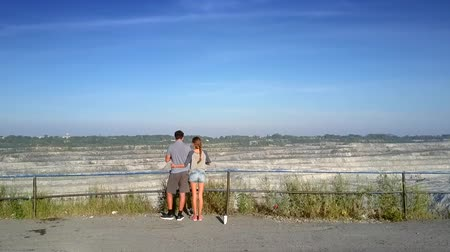bum : backside aerial view young couple on plate over huge asbestos quarry against clear blue sky in early morning