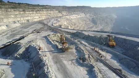 nakládané : panoramic aerial view powerful dump truck unloads rock on upper terrace of asbestos quarry in morning sunlight