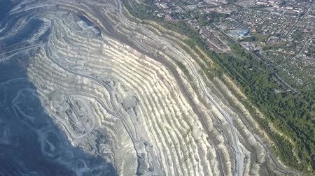 azbest : impressive high upper view asbestos open cast mining quarry near cottage town and forest in sunny morning