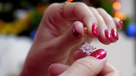 delici : slow motion close view girl with shining red manicure shows gold navel piercing banana with turning ball
