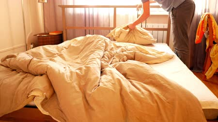 paplan : slow motion guy takes away scattered clothes of bed and makes double bed in bedroom lit with sunlight in morning