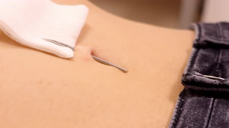 зажим : close view slow motion specialist takes away clamps leaves medical needle in navel tissue for piercing