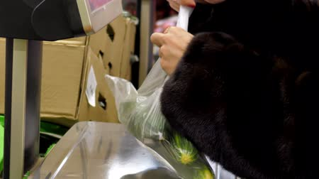 tartmak : woman in fur coat weighs chosen vegetables on automatic scales and labels price in supermarket