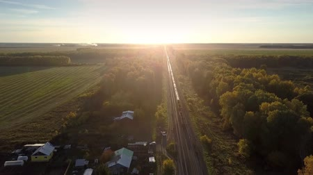 goederentrein : fantastic aerial picture long freight train moves through forest past fields village to distant horizon at bright sunset Stockvideo