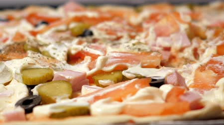 mayonez : slow motion closeup woman sprinkles herbs to raw homemade pizza with different vegetables and mayonnaise