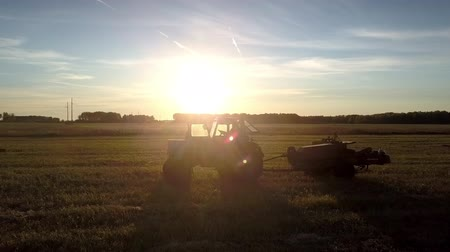bales : fantastic view tractor and square baler silhouettes drive on field in bright setting sun rays in autumn Stock Footage