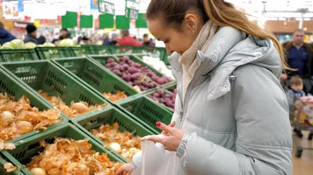 supermarket food : young blond woman in warm jacket chooses yellow onions from box and puts into disposable package at supermarket